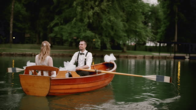Groom rowing a boat with his bride on a lake