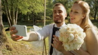 Groom taking selfies with his bride on a swing in a sunny park