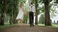 SLO MO Groom walking with bride clicking heels in joy