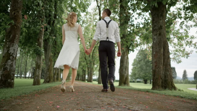 SLO MO Groom walking with his bride and clicking heels in joy