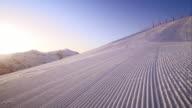 DS Groomed ski track in sunrise