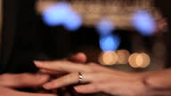 HANDHELD CLOSE UP groom's hand puts wedding ring on bride's finger as camera flashes go off