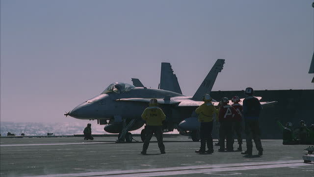 Ground crews prepare a F18 Hornet for take off from an aircraft carrier.