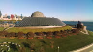 Ground level shot of Adler Planetarium lifting over dome to Chicago skyline