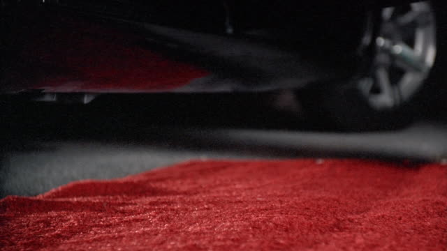 Ground-level view of red carpet / feet of woman in high heels stepping out of limo and walking down carpet as camera flashes go off