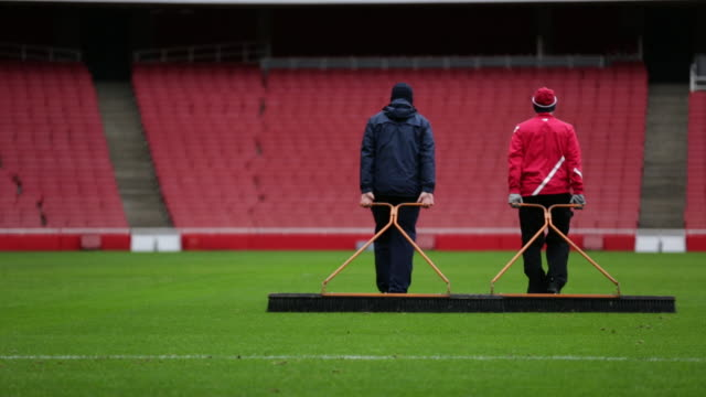 Grounds keepers for Arsenal Football Club tending to the pitch