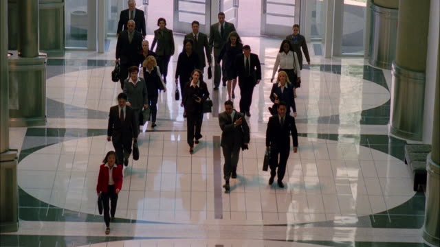 A group of adults wearing business suits enter the lobby of an office building.