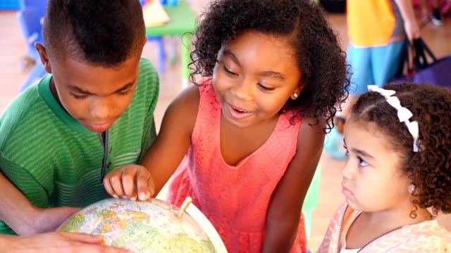 A group of African American children examine globe at daycare