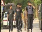 A group of armed men walk along street in Islamabad