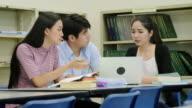 Een groep van Aziatische studenten studie en jeugdvrienden zittend aan tafel in de bibliotheek.
