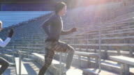 MS Group of athletes running stairs together during workout in stadium