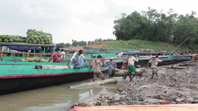 Group of bangladeshi men carrying a very heavy wooden beam at Tabalcheri float market on Kaptai Lake, Rangamati District, Chittagong Hill Tracts, Chittagong Division, Bangladesh, Indian Sub-Continent, Asia
