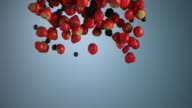 A group of berries fall through the air.