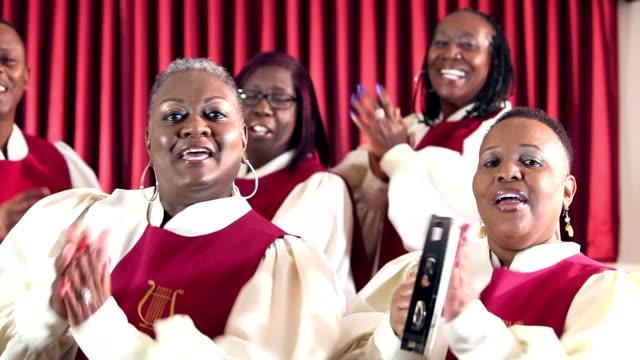 Groep van zwarte mannen en vrouwen in het kerkkoor zingen