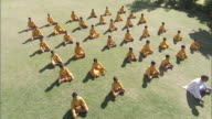 WS CS Group of boys in orange robes practicing yoga by following instructor / India