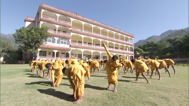WS CS Group of boys in orange robes stretching in unison / India