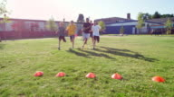 MS TD Group of boys running race on grass field during athletics class with coach and classmates watching