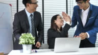 Group of business people cheering and high-five in office meeting