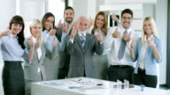 Group of business people holding up their thumbs