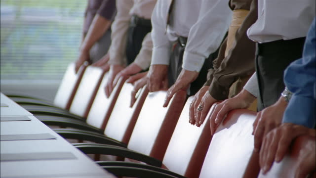 A group of businesspeople rest their hands on the backs of a row of chairs in a conference-room.