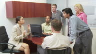 Group of businesspeople talking in crowded office