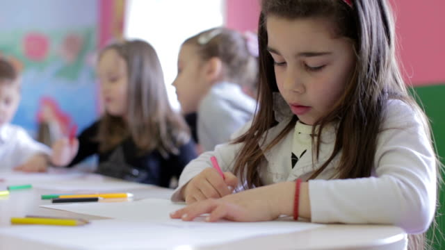 Group of children in the classroom drawing