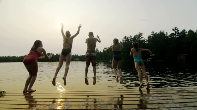 Group of children jumping off dock