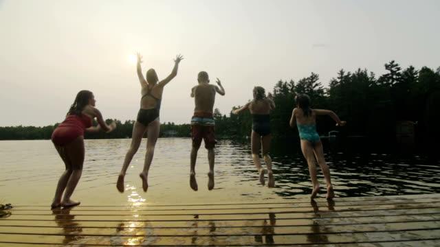 Gruppo di ragazzi saltare fuori dock