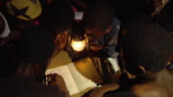 SLO MO CU HA Group of children reading by oil lamp at night, Tamale, Ghana