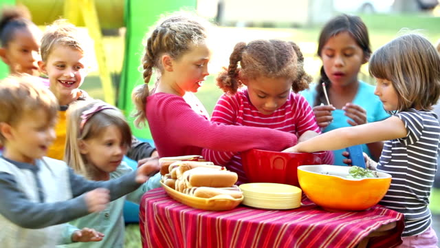 Group of children run up to table of food and eat