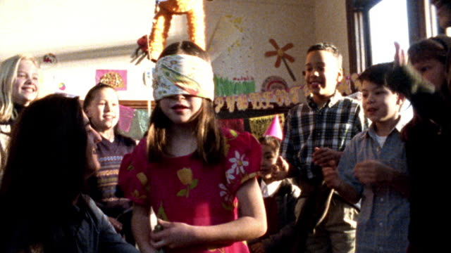 MS group of children with birthday hats clapping around blindfolded girl being spun for pinata