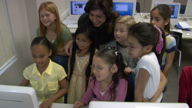 HA, Group of children (6-7, 8-9) with female teacher in computer lab, CU