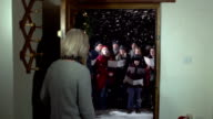 Group of Christmas Carol Singers, singing at the front door