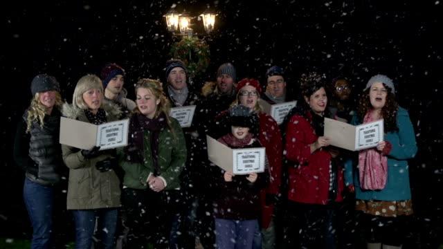Gruppe von Christmas Carol Sängern, die singt im Schnee