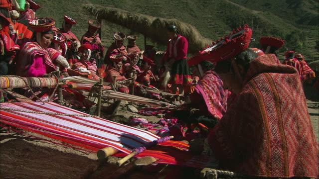 MS ZO Group of colorfully dressed Peruvian people weaving rugs on hillside / Cuzco Region, Peru