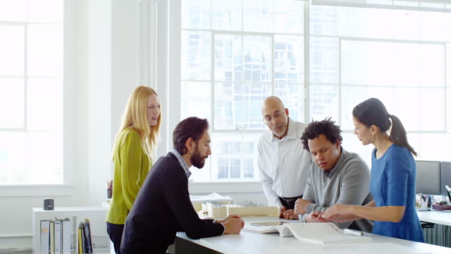 MS group of coworkers examining project on table in office workstation
