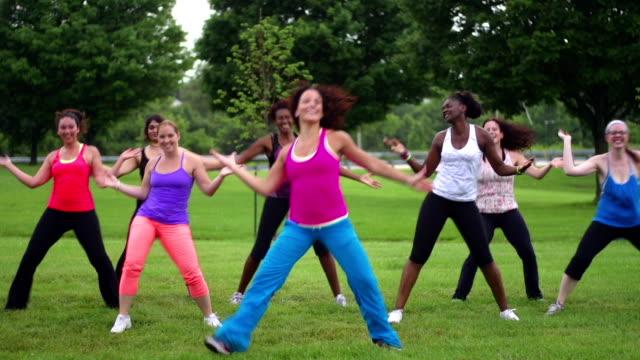 Gruppe von verschiedenen Frauen tun Zumba im Freien
