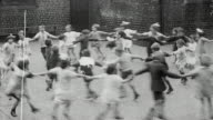 1925 MONTAGE Group of elementary school students playing Ring o' Roses on playground / Newcastle upon Tyne, England, United Kingdom