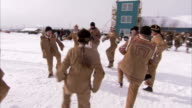 A group of Evenki people in traditional dress perform a dance in the snow. Available in HD
