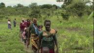 WS Group of farm workers walking on trail / Mpika, Zambia