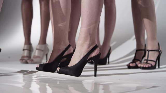 MS LA Group of female fashion models wearing high heels standing backstage before walking down catwalk