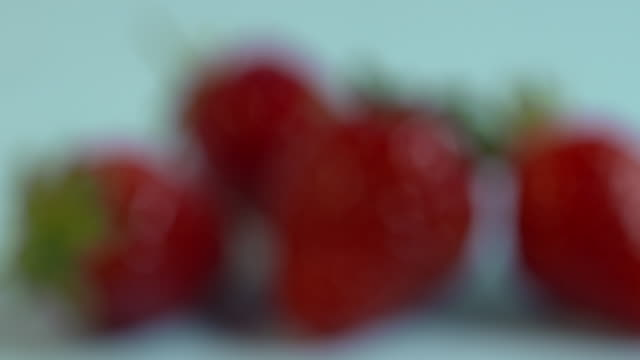 A group of four strawberries come into and out of focus.