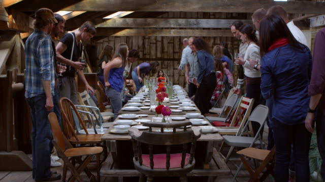 MS Group of friends and family talking and laughing while sitting down for dinner at banquet table in rustic building