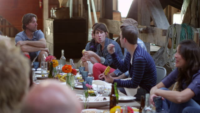 MS Group of friends and family talking while dining at banquet table in rustic building