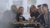 MS. Group of friends around table pose for funny smartphone selfies in local coffee shop.