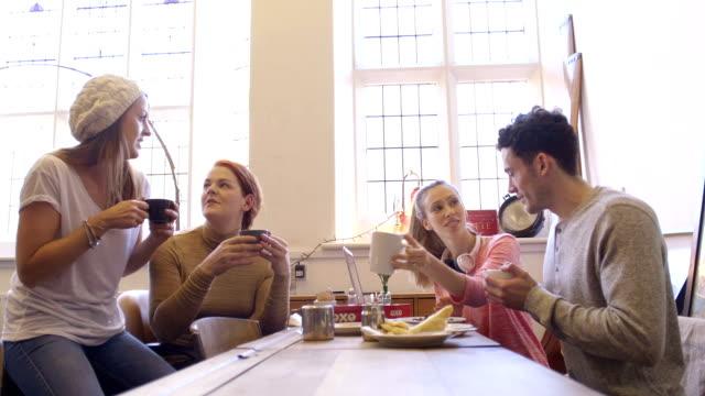Eine Gruppe von Freunden treffen bei einer Tasse Kaffee.