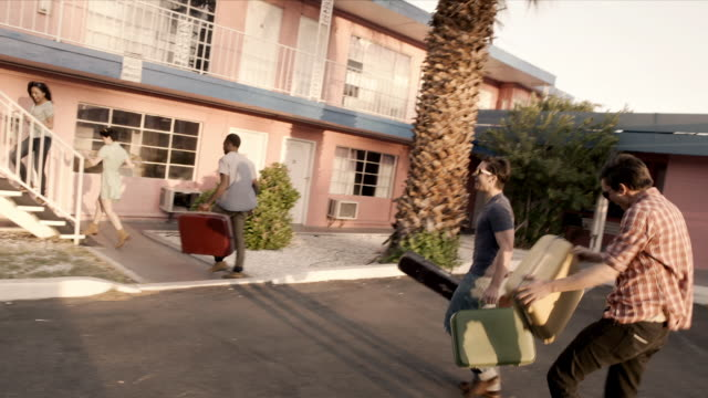 Group of friends checking in to cheap Vegas motel carry luggage upstairs to room