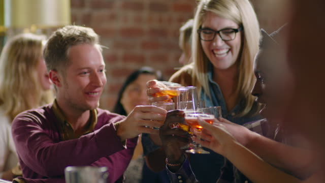 Group of friends cheers drinks and clink glasses in crowded bar