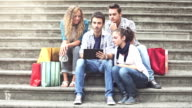 Group of friends consulting a touristic gude on digital tablet