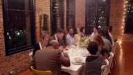 MS Group of friends dining together during party in loft
